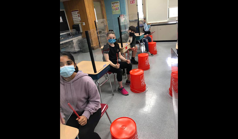 Students Sit At Their Desks Holding Drum Sticks With Buckets At Their Feet