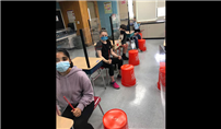 Students Sit At Their Desks Holding Drum Sticks With Buckets At Their Feet thumbnail183619